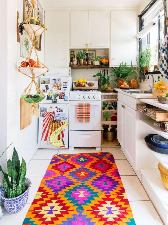 una cucina luminosa con tessuti colorati, un portafrutta in macramè e tanta vegetazione in vaso