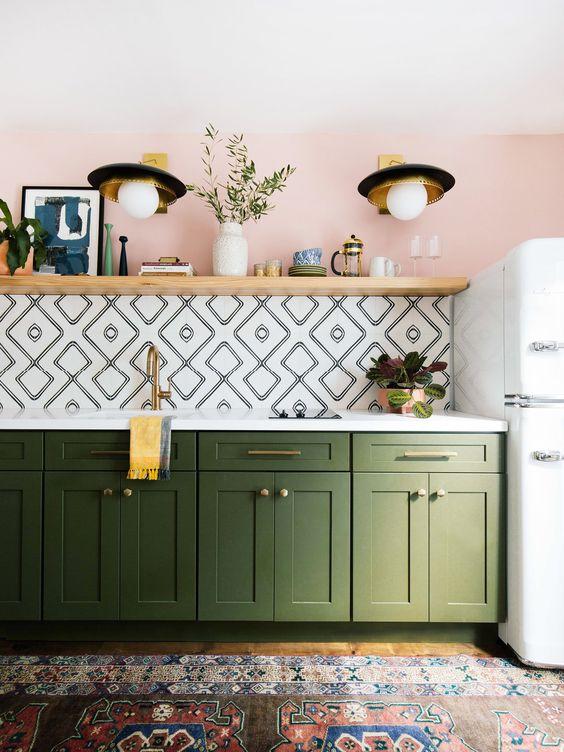 un muro rosa, un backsplash di piastrelle geometriche, armadi verdi e un tappeto boho colorato