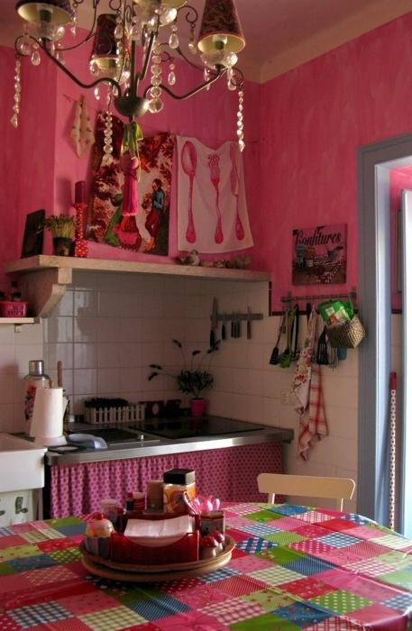 pareti rosa caldo, tessuti e un lampadario di cristallo per un boho incontra la cucina vintage