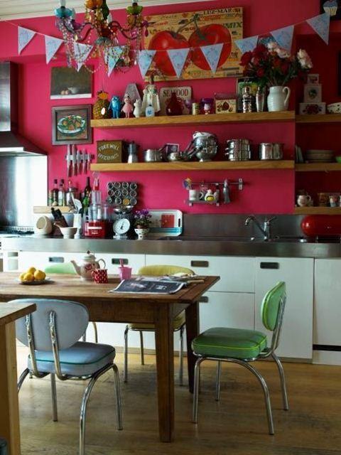 un muro rosa caldo e sedie verde e blu brillanti per uno spazio boho chic