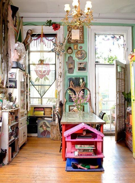 pareti verdi e mobili rosa e rossi con opere d'arte e tessuti eclettici