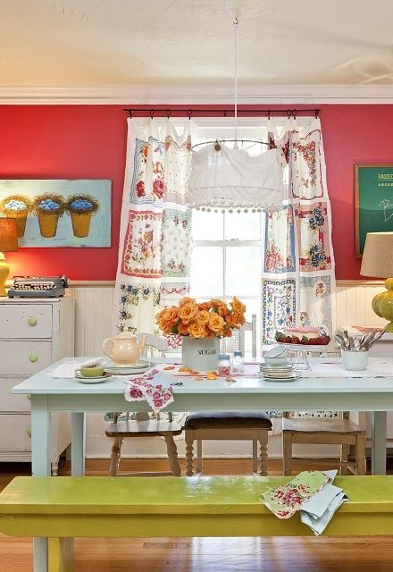pareti rosse, una panca color senape e opere d'arte e tessuti colorati per una luminosa cucina boho