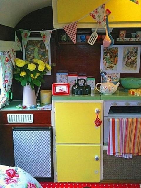 una cucina bordeaux e giallo sole più piano lavoro verdi e stoffe in tessuto