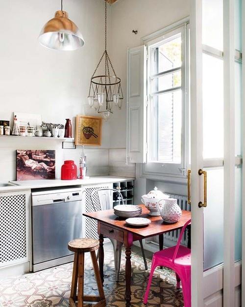 una sedia rosa neon e un barattolo rosso abbelliscono questo boho che incontra la cucina industriale