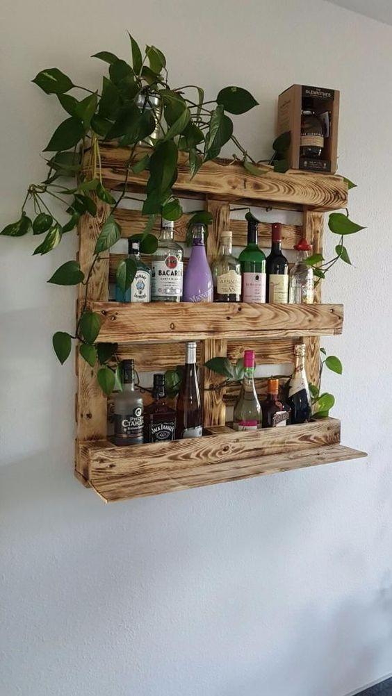 un portabottiglie macchiato di legno per pallet offre spazio sufficiente per bottiglie e piante in vaso in cima