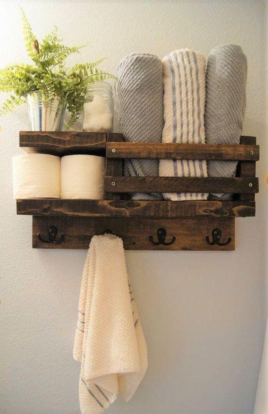 un ripiano per pallet rustico macchiato per un piccolo bagno è dotato di porta carta igienica, porta asciugamani e persino ganci per asciugamani