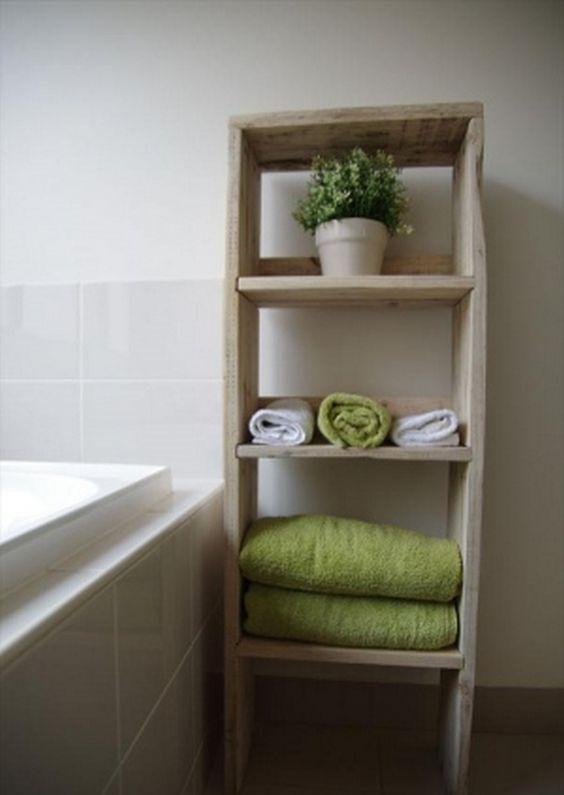 uno scaffale da bagno con più ripiani per riporre gli asciugamani e un po 'di verde in vaso costruito con pallet