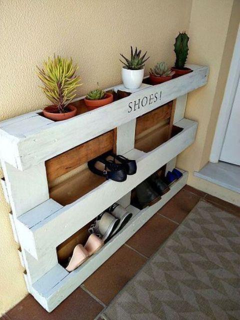 una semplice scarpiera per pallet in bianco e con parti macchiate è dotata di deposito per scarpe e deposito per vasi con piante grasse