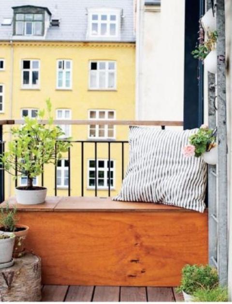 una panca in compensato nel balcone con uno spazio di archiviazione all'interno è una soluzione semplice e comoda per un piccolo balcone