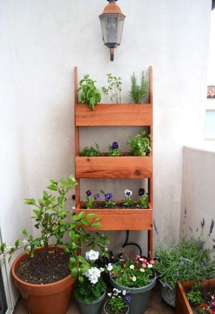 una mensola in legno a tre ripiani viene utilizzata per creare un piccolo balcone giardino