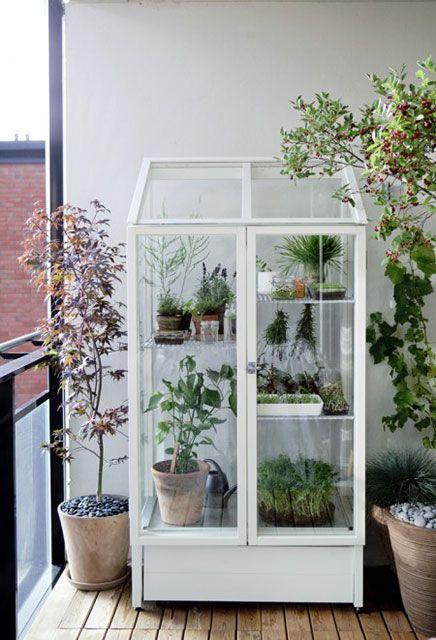 un armadio di vetro bianco come una casa grena per un balcone, posiziona le piante e i fiori in vaso lì