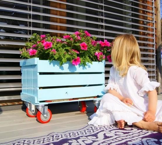 una cassa blu su rotelle può essere utilizzata per posizionare alcune fioriere o qualsiasi altra roba da riporre