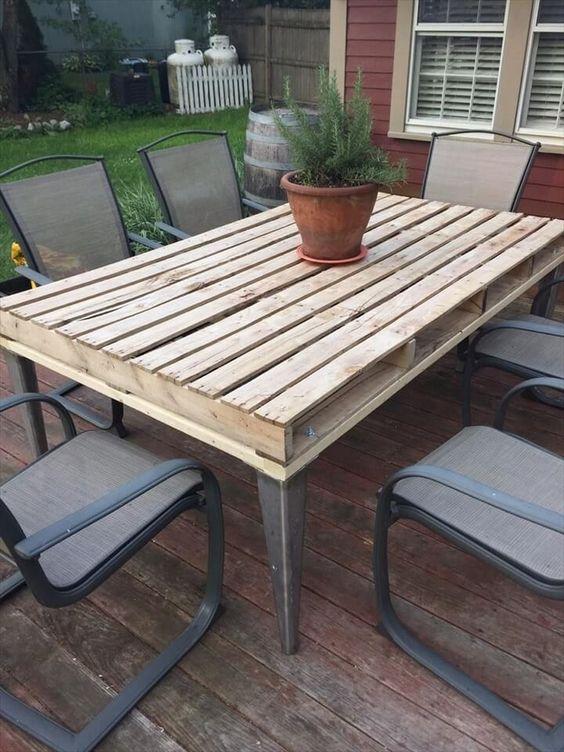 costruisci un tavolo con pallet da esterno con un piano del tavolo rustico e gambe in metallo e trova alcune sedie abbinate