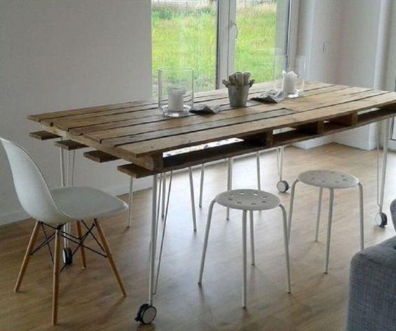 un tavolo da pranzo contemporaneo con un pallet come piano del tavolo e gambe a forcina su ruote più moderne sedie bianche
