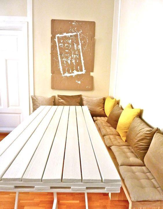 un tavolo da pranzo bianco con un piano del tavolo composto da un unico pallet su sottili gambe in metallo è un'idea audace e contemporanea
