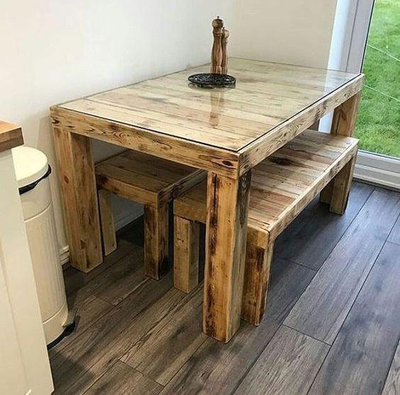 un tavolo da pranzo rustico con un tavolo in legno pallet con un piano in vetro e panche abbinate, tutte colorate in una tonalità chiara