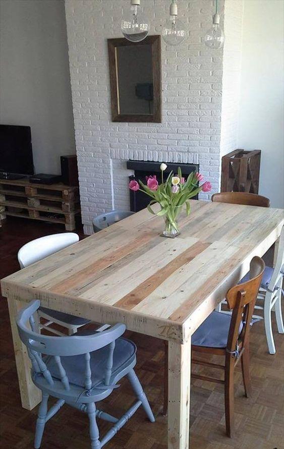 un tavolo da pranzo neutro in legno di pallet macchiato e sedie non corrispondenti per uno spazio da pranzo eclettico