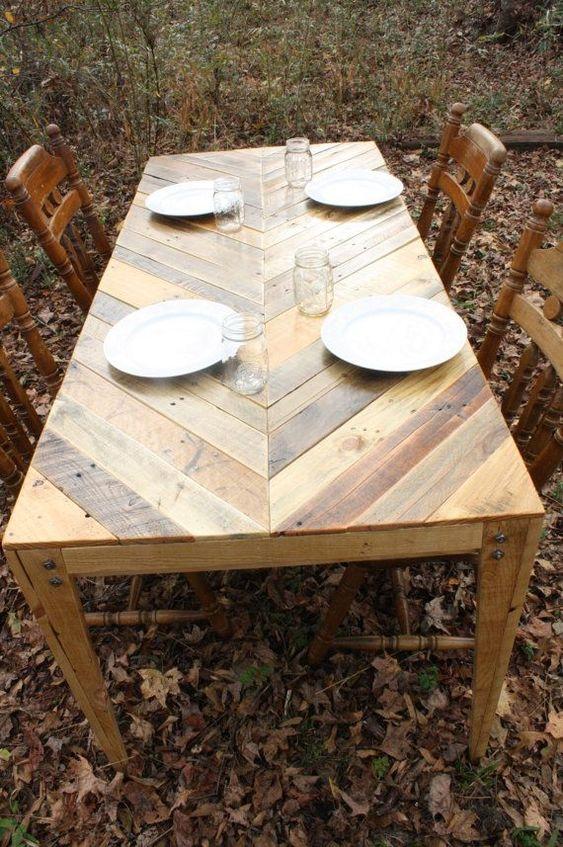 un tavolo da pranzo all'aperto con un motivo a chevron sul ripiano del tavolo completamente costruito in legno di pallet e sedie vintage