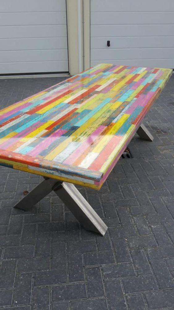 un tavolo da pranzo in pallet colorato con un piano in resina e comode gambe a cavalletto è un'idea unica