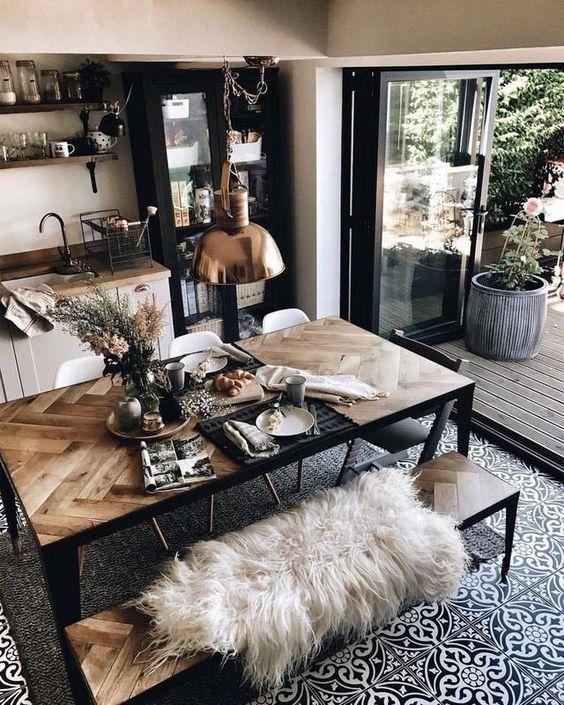 uno splendido tavolo da pranzo con un ripiano rivestito di chevron in legno di pallet e cornici in metallo nero e panche abbinate per uno spazio boho