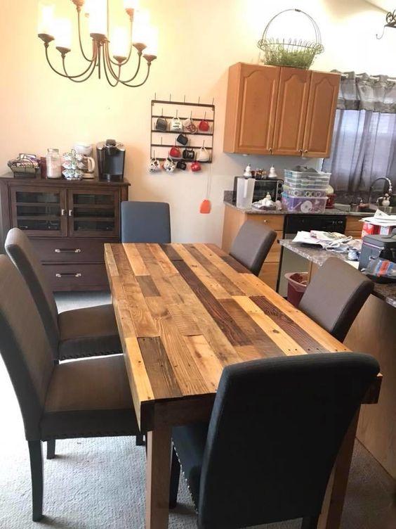 un tavolo da pranzo rustico multicolore costruito in legno di pallet e sedie imbottite per uno spazio da pranzo chic
