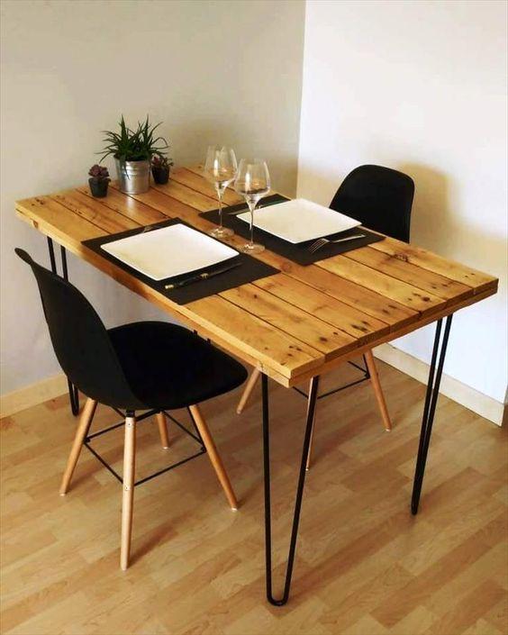 un tavolo da pranzo piccolo e comodo con un tavolo in pallet e gambe a forcina nere sembra molto chic, le sedie nere si aggiungono ad esso