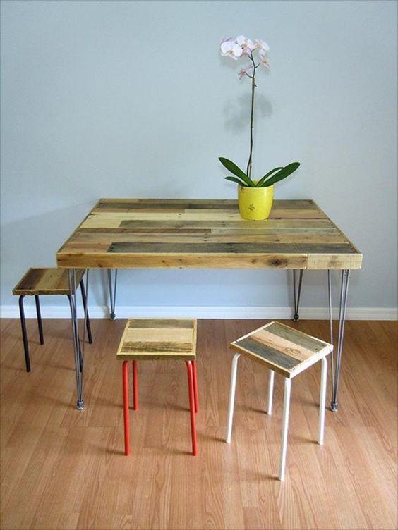 un tavolo da pranzo rustico con un tavolo in legno di pallet su gambe a forcina e alcuni sgabelli abbinati