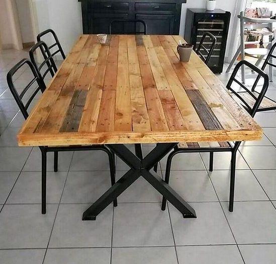 un elegante tavolo da pranzo con gambe incrociate in metallo e un tavolo in legno di pallet e sedie in metallo nero