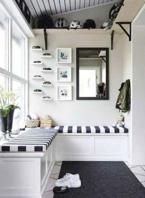 uno spazio monocromatico con una panca incorporata a strisce, un tappeto e alcuni ripiani per la conservazione