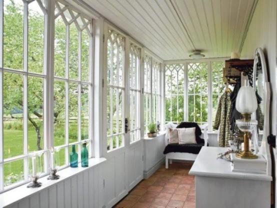 una veranda vintage con alcune sedie, mobili contenitori e piante in vaso