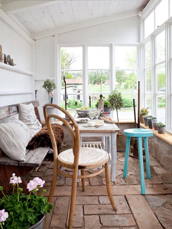 una veranda vintage scandinava con una comoda panchina e un lungo davanzale con fiori in vaso e vegetazione e un tavolo da pranzo in legno