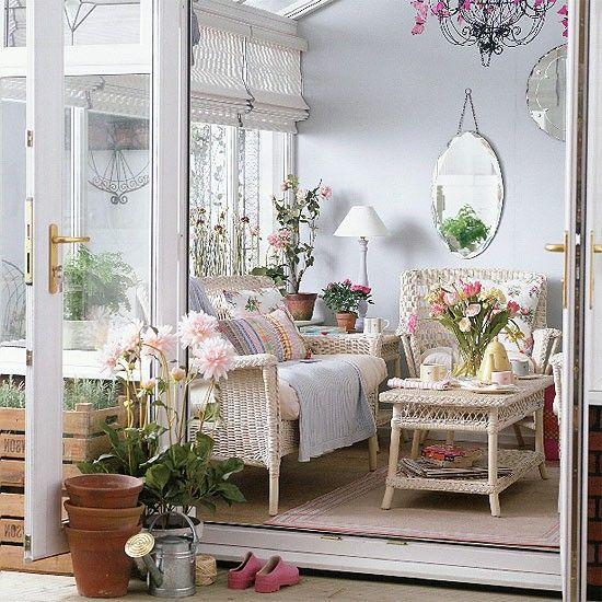 una veranda tradizionale con mobili in vimini bianco, tessuti stampati e colorati, lampade, specchi e fiori in vaso