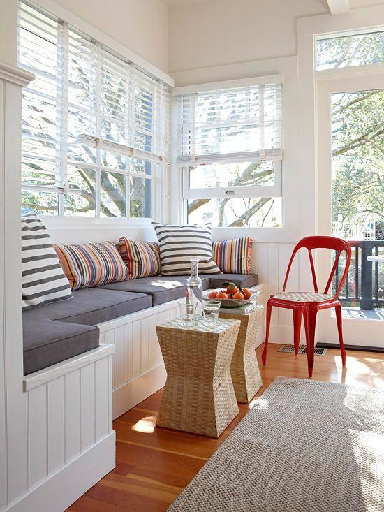 un piccolo soggiorno veranda con una grande panca incorporata con ripostiglio e un duo di sgabelli in vimini
