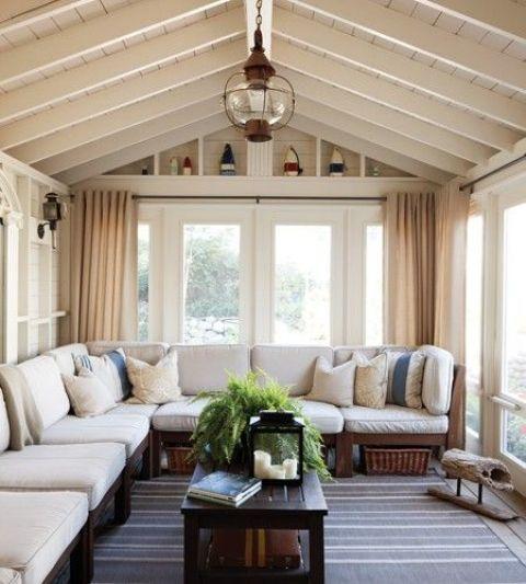 un'accogliente veranda tradizionale con una grande panca tradizionale con tappezzeria, cuscini e tende più un tavolino da caffè con pallet