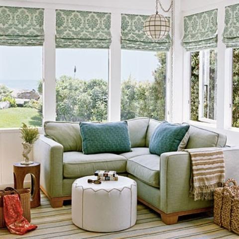 un rinfrescante angolo veranda con sfumature verdi e mobili, comodi pouf e tocchi colorati