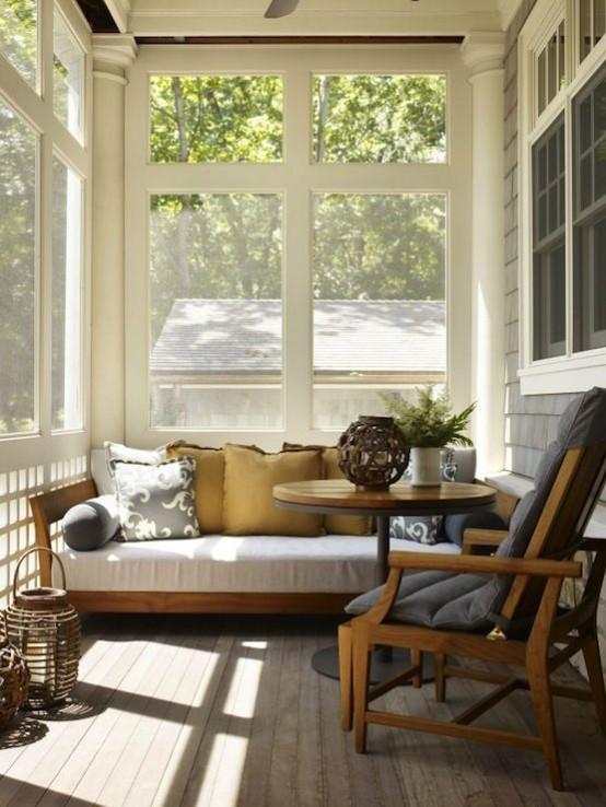 una piccola veranda moderna della metà del secolo con alcuni mobili confortevoli, lampade in vimini e piante in vaso