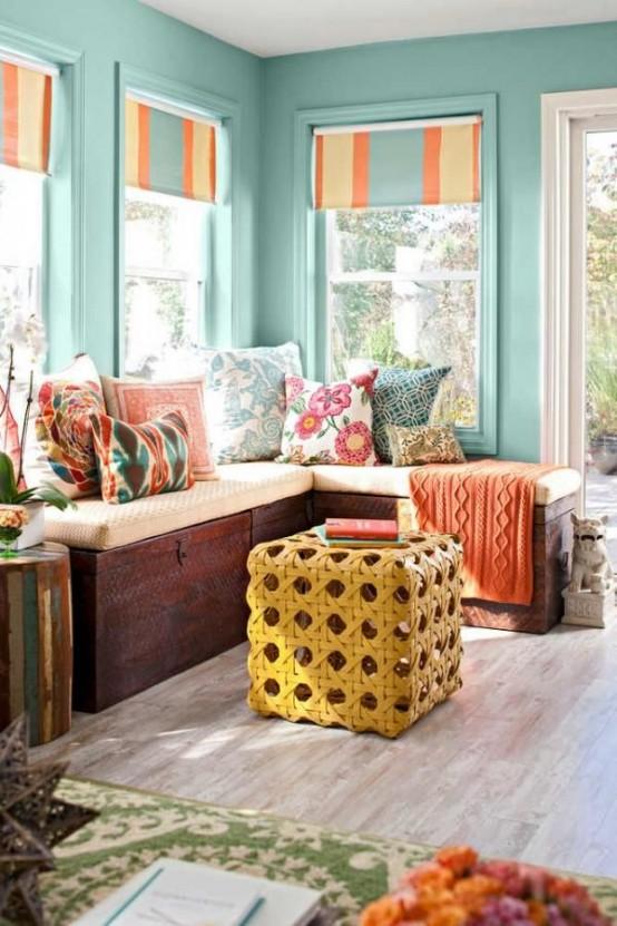 una veranda piccola e colorata con pareti turchesi, dettagli colorati e stampati e un ottomano in vimini