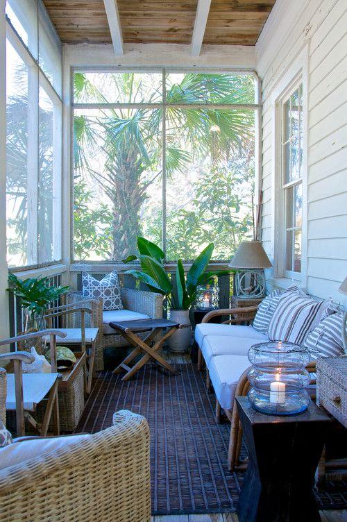 una piccola veranda di ispirazione tropicale con mobili in legno, sedie in vimini, piante in vaso e lampade