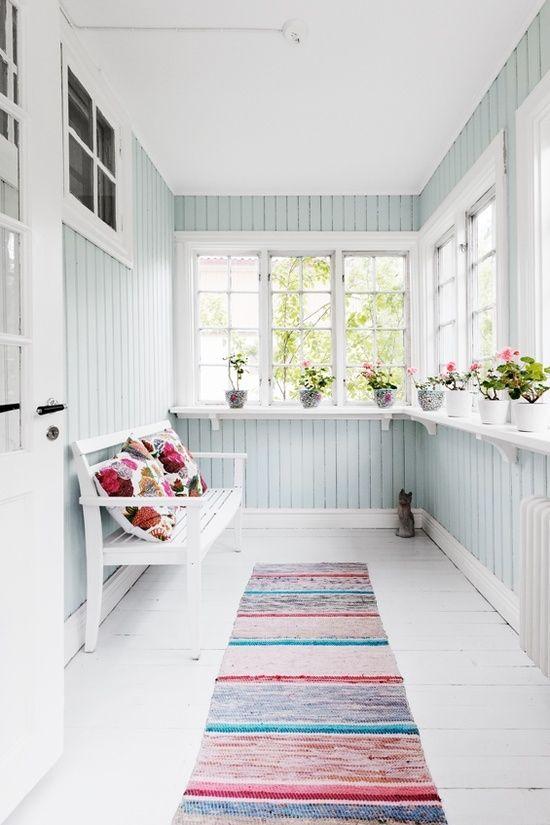 una piccola veranda pastello in una leggera tonalità acqua, tessuti colorati e una panchina più fiori in vaso