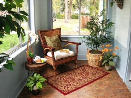 un accogliente angolo veranda con piante in vaso e fiori e mobili e accessori in vimini più un tappeto