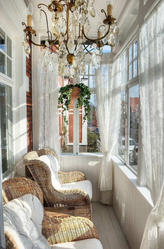una veranda di ispirazione vintage con un grande lampadario di cristallo, tende di pizzo e sedie di vimini