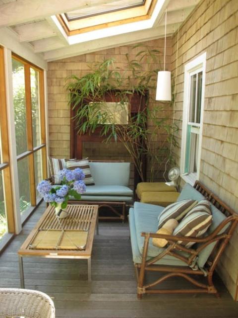 una veranda moderna della metà del secolo realizzata in tonalità sabbia, con sedie in rattan, lampade a sospensione e vegetazione in vaso