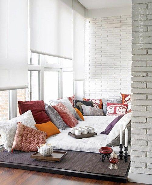 un angolo veranda chic contemporaneo con un posto a sedere proprio sul pavimento e molti cuscini per un'atmosfera boho
