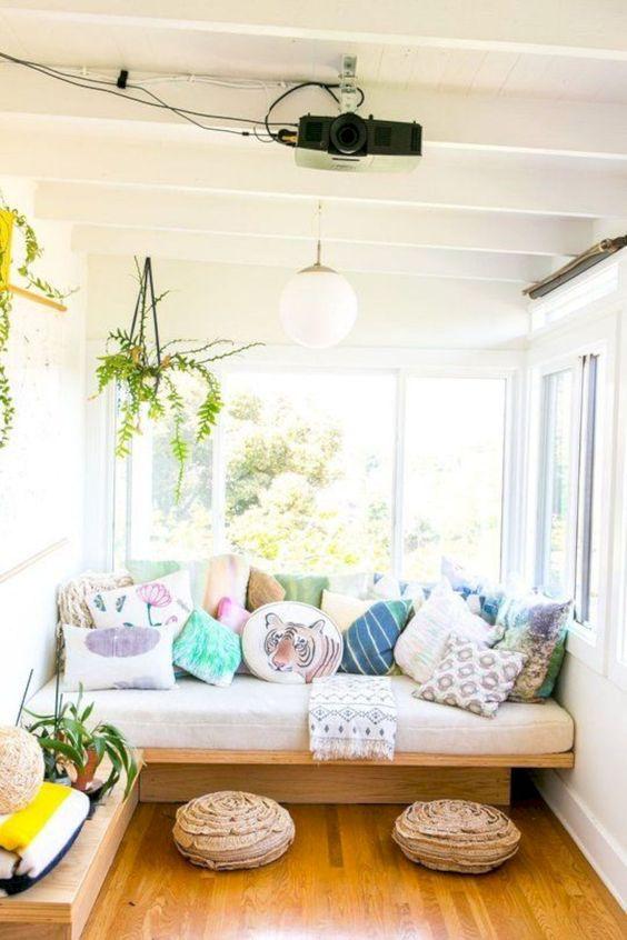 un'accogliente veranda con divano e tanti cuscini, con poggiapiedi e piante in vaso