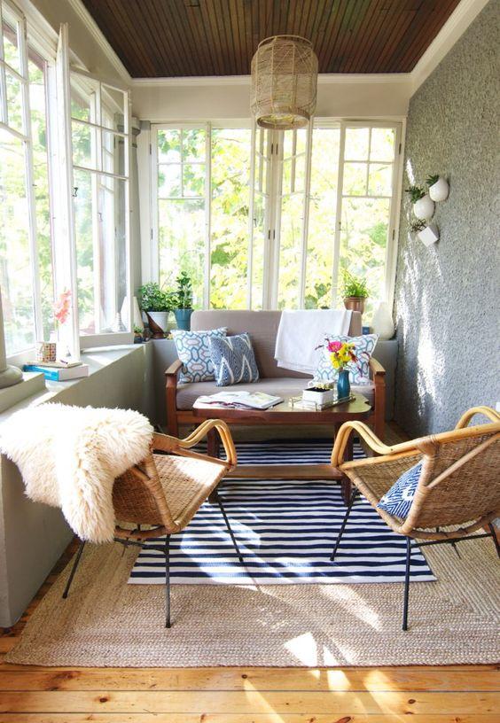 una veranda eclettica e boho con sedie e lampade di vimini, con tappeti a strati e tocchi di colore