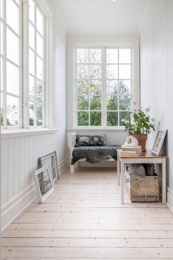 una piccola veranda ariosa con una panchina, un tavolo con una cassa e alcune opere d'arte è uno spazio accogliente