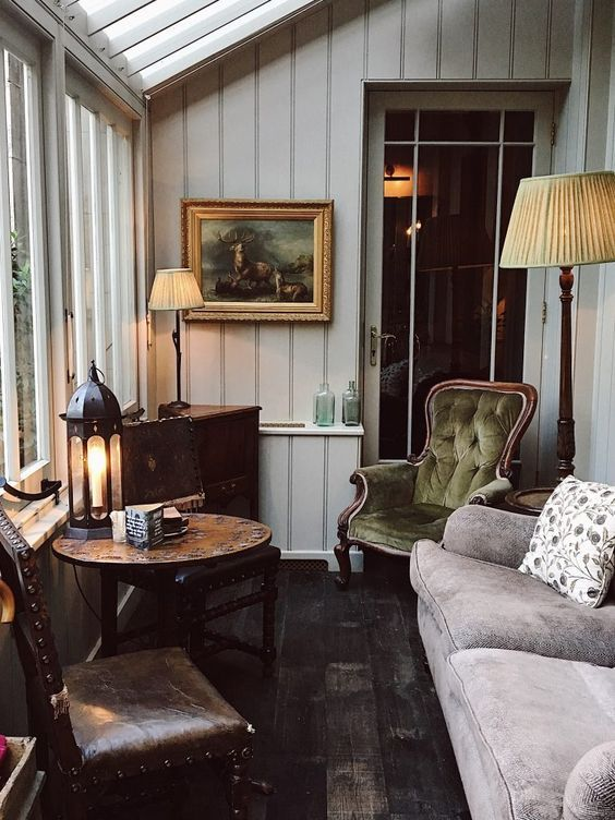 una veranda d'ispirazione vintage con mobili raffinati, alcune lampade e una lanterna, un'opera d'arte e una credenza