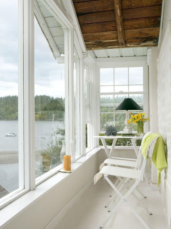 una piccola veranda accogliente con alcune sedie pieghevoli e un tavolo, fiori, lampade e candele