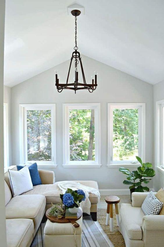 una veranda piccola e accogliente con mobili neutri, un paio di pouf e un po 'di verde sembra un soggiorno aggiuntivo
