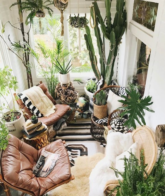 una veranda lussureggiante boho con sedie in pelle, molta vegetazione in vaso e alcuni tocchi di vimini e tessuti